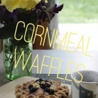 CORNMEAL WAFFLES on white plate with bottle of maple syrup and place setting