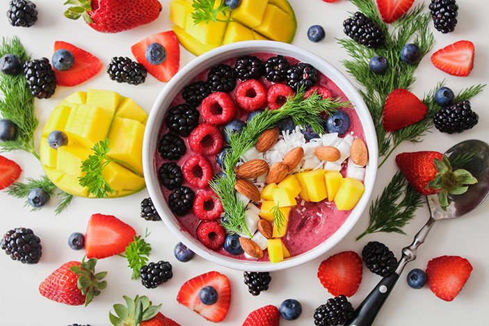 Smoothie in white bowl topped with blackberries, raspberries, coconut, mango chunks on white board with berries