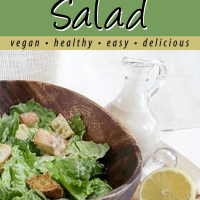 Vegan Ceasar Salad in wood salad bowl with ceasar dressing in glass container