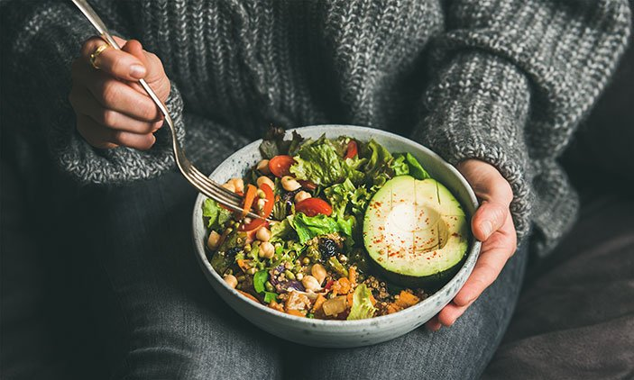 Girl in jeans holding a vegetable bowl