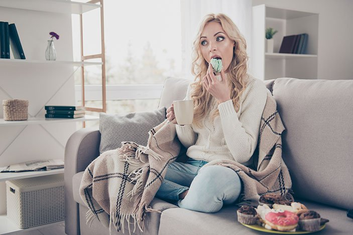Attractive women in jeans with a cup of coffee eating sweets on a couch
