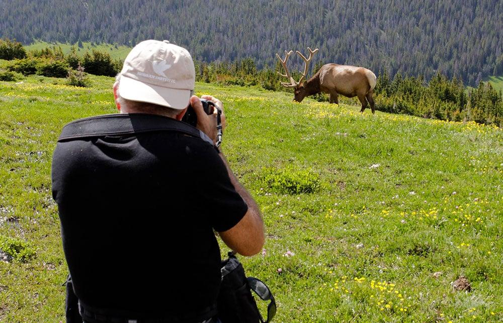 Charles holding camera shooting an elk